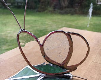 Standing Snail Stained Glass suncatcher on a green leaf