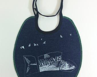Bavoir pour bébé en denim bleu avec surjet de couleurs variées, imprimé de poisson stylisé