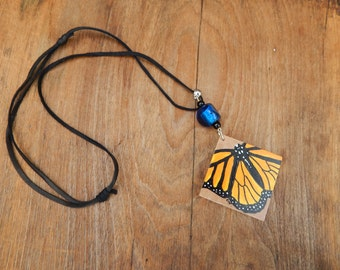 Monarch butterfly pendant hand painted slip knotted black leather cord