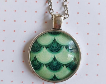 Cabochon pendant necklace featuring sea green scalloped design on a silver base and chain