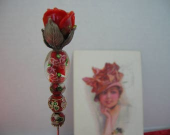 A red glass flower bud is the top of this hat pin