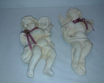 A Vintage pair of 2 plaster wall hanging cherubs angels playing music with a pink ribbon and dried flowers around their neck, color white