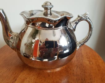 very old porcelain silver plated Teapot. comes with authentic valuation certificate