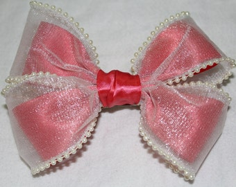 two bows in one, its a large beige lace bow with a pink ribbon bow inside.