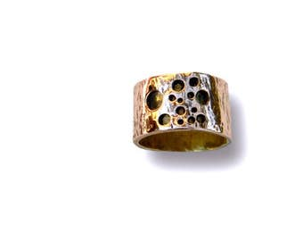 copper ring, brass. copper pierced with holes of different diameters and virolle brass ring made entirely by polite hand mirror