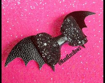 Glittery bat shaped hair bow.