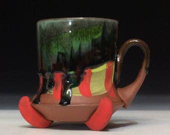 red feet and stripes with copper green and black glazes dripping coffee mug