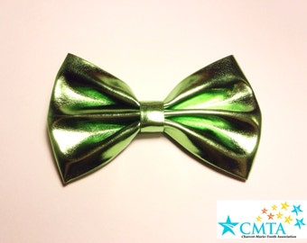 One green faux leather hair bow. Portion of sale goes to charity. Cruelty-free.