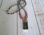 Beautiful rectangle glass tile necklace with silver toned edging with seed beads and shell beads and bird clasp