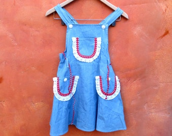 Vintage 1960s 1970s Girl's Blue Denim Pinafore Overalls Dress with white eyelet and red polka dot trim. Size 6 7 8