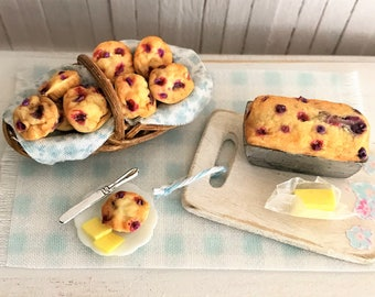 Miniature Blueberry Muffins, A Blueberry Loaf Cake, Butter, And A Shabby Cutting Board