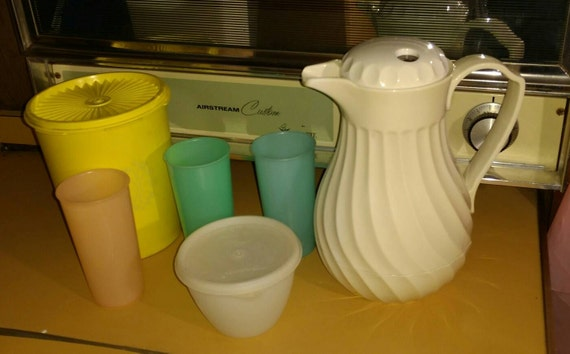 A group of vintage Tupperware and a Corning caraf.  Three tumblers, sugar bowl with lid, and canister.  Perfect for your camper or cabin.