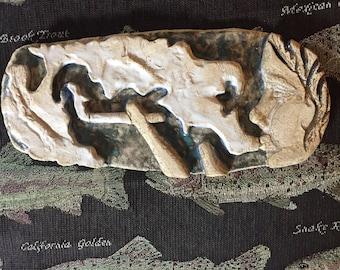 Flat clay sculpture of a girl smoking