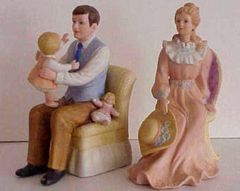 2 Charming Bisque Figurines 1 of a Father holding the Baby 1 the Mother both Marked with Crossed Swords and Numbered