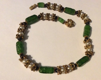 1950 choker glass beads surrounded by gold tone findings.  Lovely mid century classic green, white and black beaded necklace.