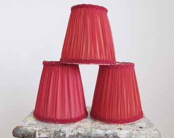 Three gorgeous vintage red fabric pleated lampshades with braid trim.