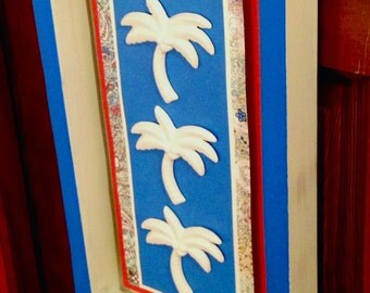 Ceramic Palm Tree Shadow Box Wall Hanger Displayed on Layered Paper Accents in a Distressed Wooden Frame at Crafts by the Sea