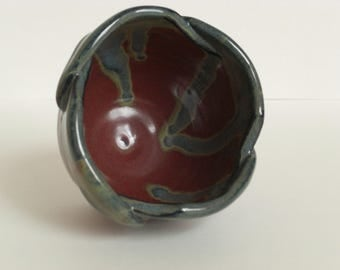 Altered red handmade ceramic bowl with blue accents