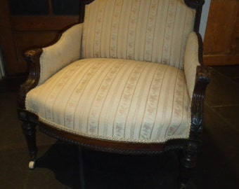 Antique French upholstered bergere salon chair with show frame and white casters
