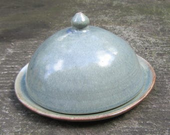Handmade ceramic cheese plate with rounded cover with variegated blue glaze
