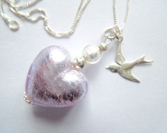 A silver Murano glass heart pendant with sterling silver bird charm and chain.