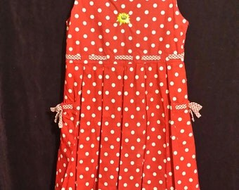 An adorable littie girl red/ white polk-a-dot dress, with two side tie  string pockets.