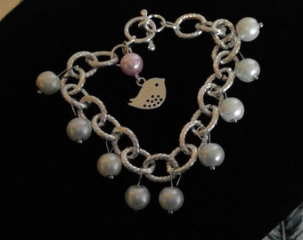 silver bird with white and pink pearl bracelet