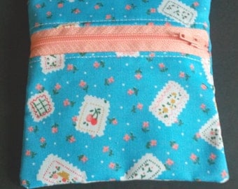 A pale blue, polycotton zipper front opening coin purse/pouch with white & peach floral designs, peach zip,