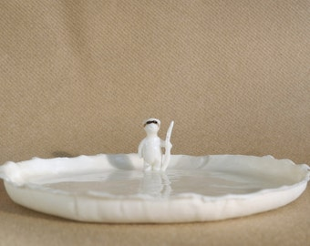 Spoon rest in white porcelain with a bear in a mask holding a stick