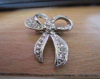 """vintage silvertone bow brooch studded with clear stones 1.75""""high 1.5""""wide in good condition"""