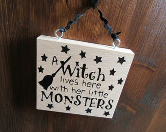A witch lives here with her little monsters. Real wood, solid beech wooden hanging plaque. Witch sign. Witch plaque. Xmas. Halloween.