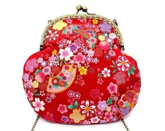 Red Japanese bag with a bronze metal clasp, patterned with pink and white cherry blossoms