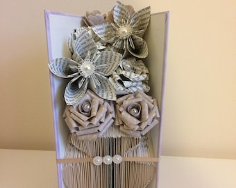 Folded book art vase and selection of flowers