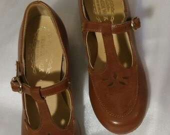 Carmel brown t-strap dress shoe. Leatherlike with suede cut out over instep. Metal buckle.Wedge heel,rubber sole  Sz ,9 , 1 1/2