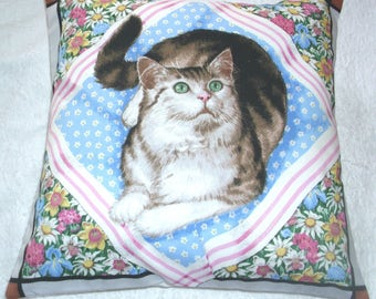 Lovely grey and white Tabby cat on a blue and white spotted sheet cushion