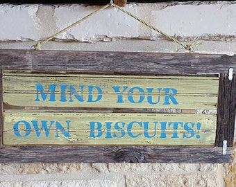 "Repurposed shipman sign with old fence wood frame, ""Mind your own biscuits."""