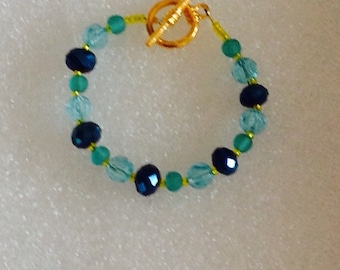 Bracelet with gold toned toggle clasp, navy faceted beads, aqua faceted crystals and aqua frosted glass beads.