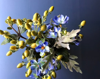 Silk flowers and olives in yellow mug