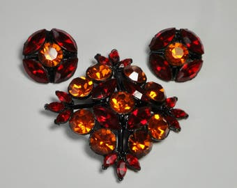 WEISS Japanned Black Metal with Red and Orange Rhinestones Brooch and Earrings Set.