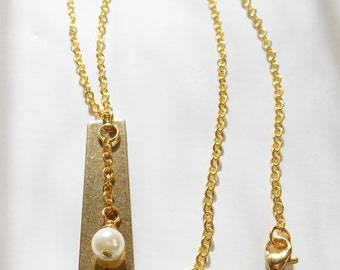 Gold Metal Pendant with a Star Cut Out and Small White Pearl Glass Bead Hanging From a Gold Chain