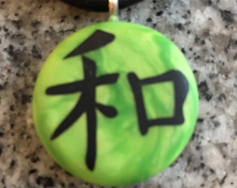 PEACE Japanese kanji symbol hand carved on a polymer clay green pearl color background. Pendant comes with a FREE necklace