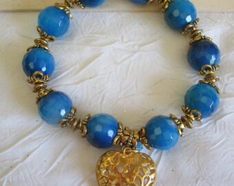 Bracelet en perles de Jade bleu avec un coeur doré.