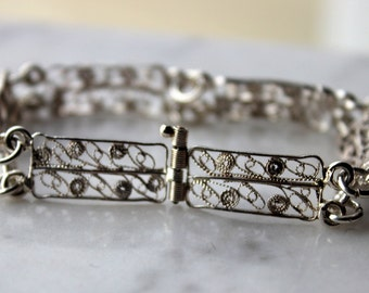 Vintage silver filigree panel link bracelet.7.6 grams silver-6 5/8 inches long 6 panels 3/8 inch wide barrel clasp.excellent condition1960's