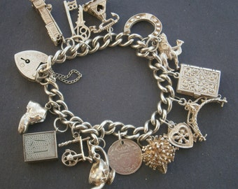 B921) A lovely old antique vintage hallmarked sterling silver 17 charm chain bracelet with padlock and safety chain.