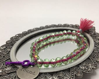 Green with Pink Center Faceted Glass beaded flexible bracelet with a Round Antiqued Silver FOUND charm & Purple Key and Pink Tassel.