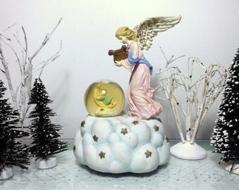 """Music Box Snow Globe plays """"Jesus Loves the Little Children."""" Heavenly Angel, Baby Child on Moon. The San Francisco Music Company. Sparkles"""
