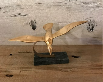 Brass bird on marble stand. Brass flying bird.