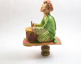 "Lamp Finial, Little Drummer Boy on his ""Magic Carpet"".  Lampshade Finial; (14C)"