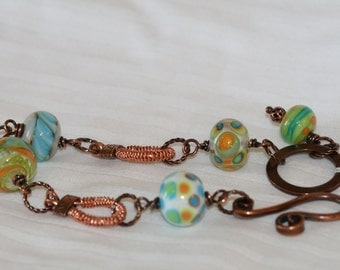Antique copper bracelet with green and blue glass beads