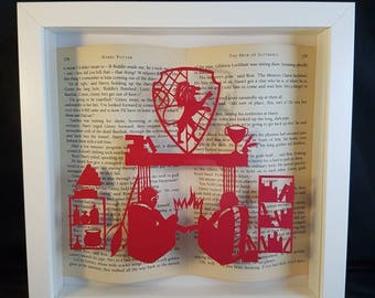 Harry Potter papercutting framed with book pages. Harry and Ginny by the fire after a Griffindor quidditch match